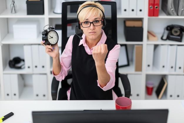 Uma jovem mulher sentada em uma mesa de computador e segurando um despertador.