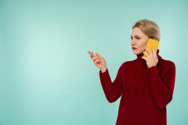 Uma jovem mulher séria com um suéter vermelho e um smartphone em um fundo azul