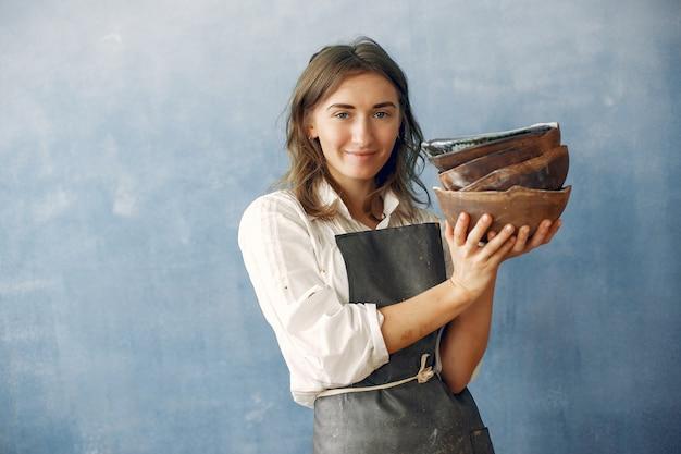 Uma jovem mulher tem um prato de cerâmica nas mãos