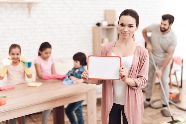 Uma jovem mulher tem uma placa branca nas mãos dela.