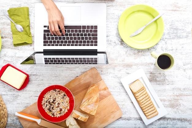 Uma jovem mulher tomando café da manhã enquanto usa um computador laptop.