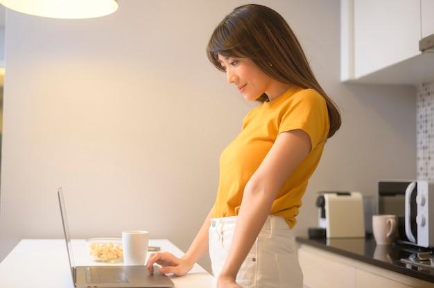 Uma jovem mulher trabalhando com seu laptop e tomando uma xícara de café, estilo de vida e conceito de negócio