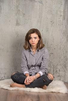 Uma jovem mulher triste em uma camisa xadrez soprando suas bochechas.