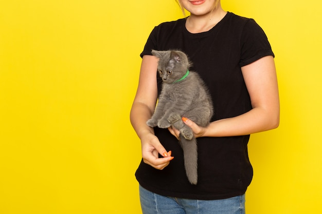 Uma jovem mulher vestida de preto segurando um gatinho fofo em amarelo