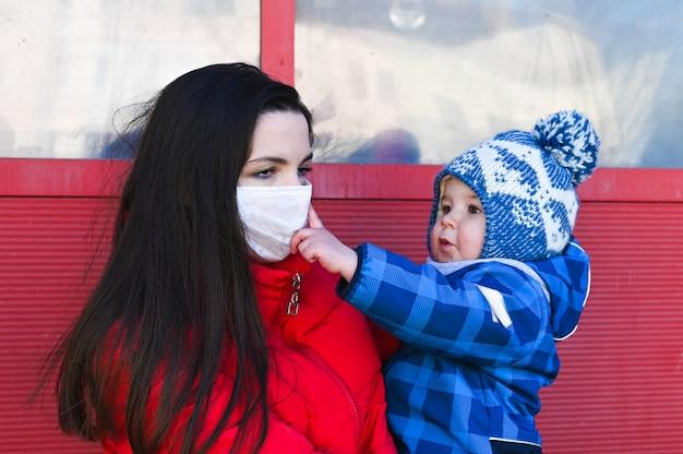 Uma jovem mulher vestindo uma máscara facial e segurando nas mãos um garotinho. medidas protetoras. mãe e filho em quarentena.