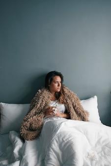Uma jovem na cama com um cobertor está bebendo chá quente