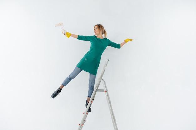 Uma jovem na escada pinta uma parede branca com um rolo. reparação do interior.