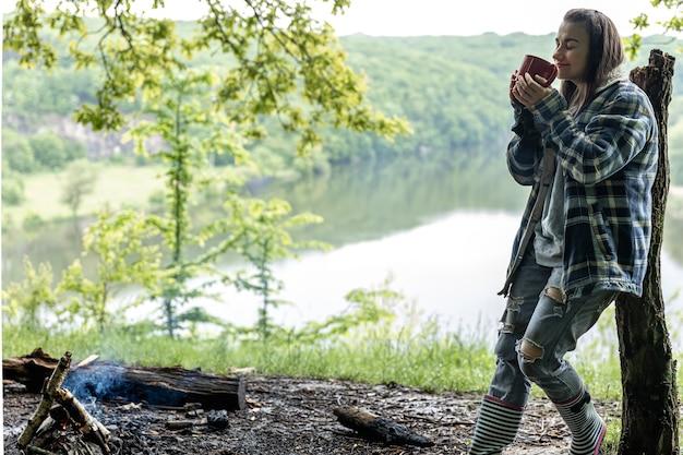 Uma jovem na floresta perto do rio se aquece perto do fogo e bebe uma bebida quente.