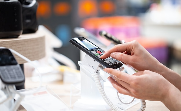Uma jovem na loja está de pé perto do estande e escolhe um telefone