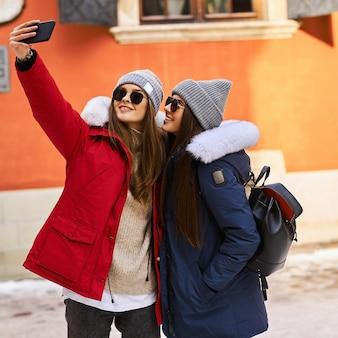 Uma jovem na moda swalks e se divertir na cidade no christmastime