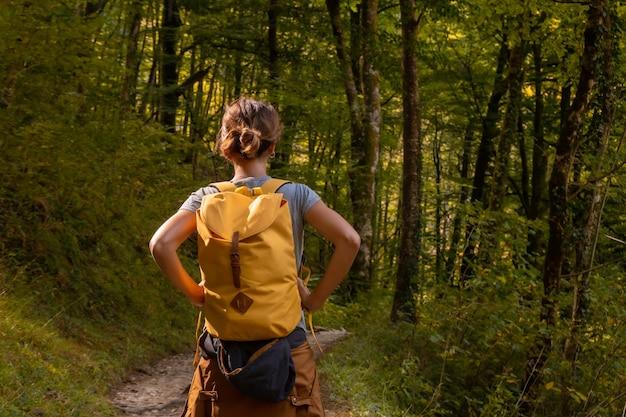 Uma jovem na trilha em direção a passerelle de holtzarte de larrau na floresta ou selva de irati, no norte de navarra na espanha e nos pirineus atlânticos da frança