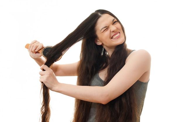 Uma jovem não pode pentear o cabelo emaranhado problemático. no branco isolado perto acima
