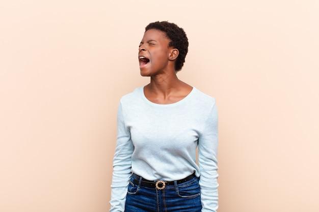 Uma jovem negra bonita gritando furiosamente, gritando agressivamente, parecendo estressada e com raiva