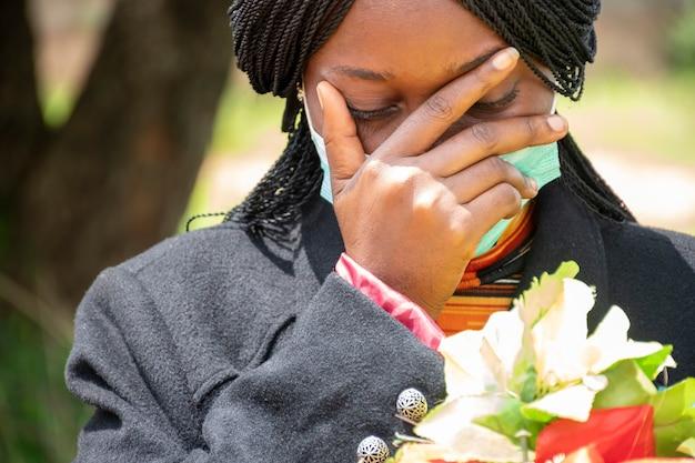 Uma jovem negra de luto, vestindo preto e segurando flores