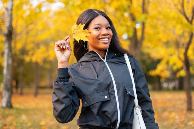 Uma jovem negra linda e feliz com um sorriso fofo em roupas da moda casuais segurando uma folha amarela de outono está caminhando no parque com uma folhagem de outono colorida brilhante