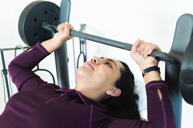 Uma jovem no banco de peso fazendo exercícios