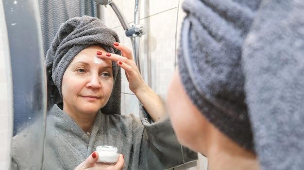 Uma jovem no banheiro, logo após o banho, com uma toalha enrolada na cabeça. aplicar o creme no rosto.