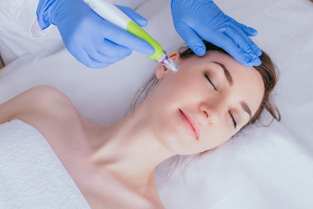 Uma jovem no consultório de cosmetologistas recebe mesoterapia fracionada para o rosto