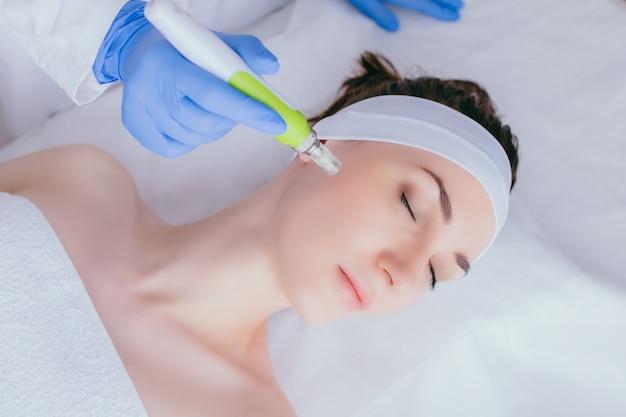 Uma jovem no consultório de cosmetologistas recebe mesoterapia fracionada para o rosto.