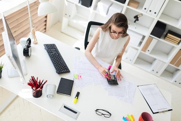 Uma jovem no escritório detém um marcador-de-rosa na mão e conta com uma calculadora.