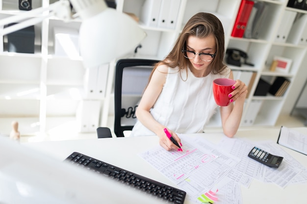 Uma jovem no escritório detém um marcador-de-rosa, uma caneca vermelha e trabalha com documentos.