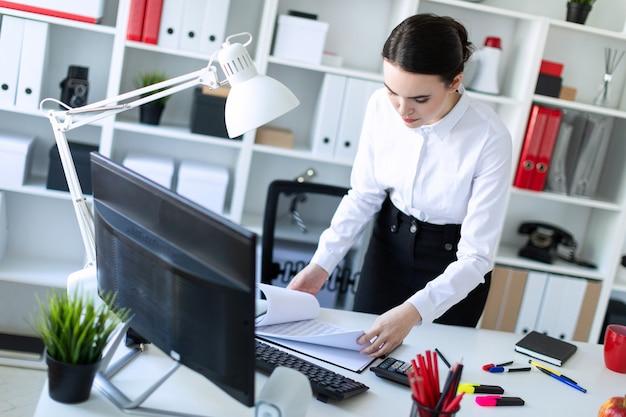 Uma jovem no escritório está de pé perto da mesa e olha através dos documentos.