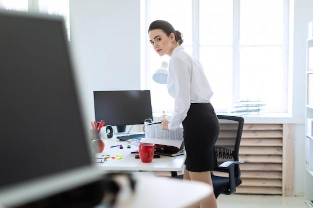 Uma jovem no escritório está de pé perto da mesa, segurando um lápis na mão e folheando a pasta com os documentos.