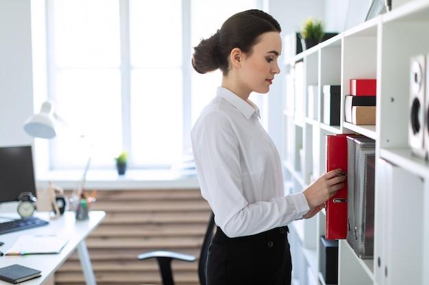 Uma jovem no escritório está de pé perto da prateleira e puxando uma pasta vermelha.