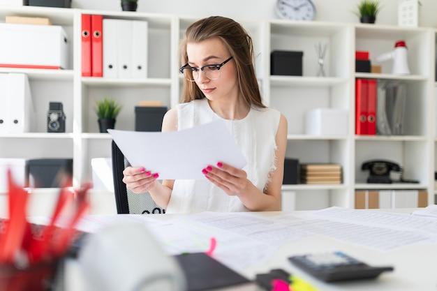 Uma jovem no escritório está segurando uma folha