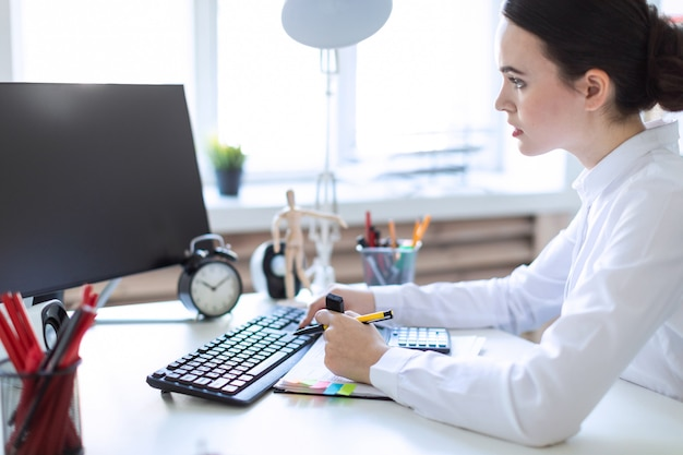 Uma jovem no escritório se senta em uma mesa, trabalha com um computador, calculadora, documentos e detém um marcador e uma caneta na mão esquerda