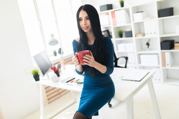 Uma jovem no escritório sentou-se na mesa e segurava um copo vermelho nas mãos.