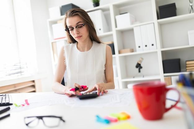 Uma jovem no escritório tem um marcador rosa na mão e conta com a calculadora.