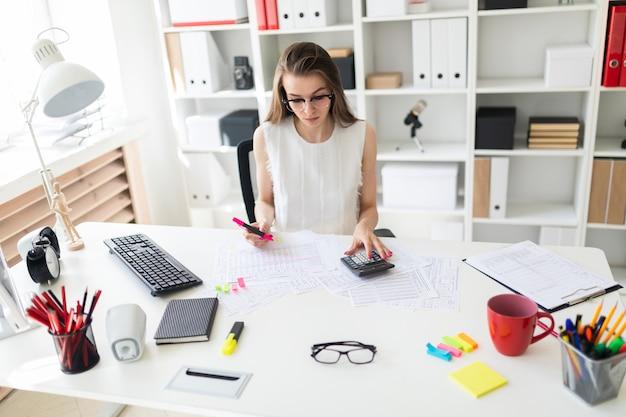 Uma jovem no escritório tem um marcador rosa na mão e conta com uma calculadora.