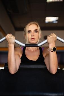 Uma jovem no ginásio está envolvida, mãos fortes levantam a barra com peso, um olhar focado e cumprimento de metas.