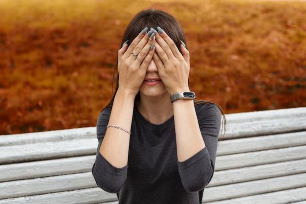 Uma jovem no parque cobriu o rosto com as mãos