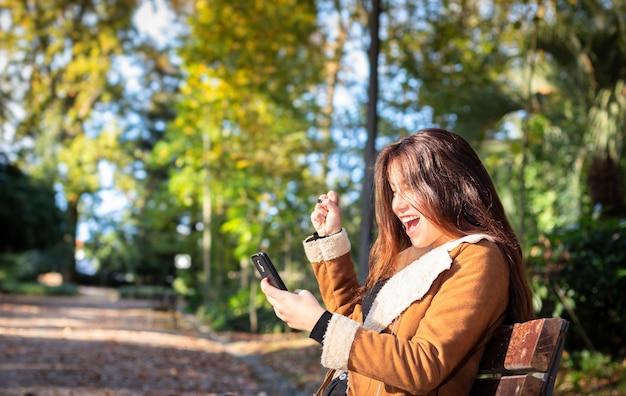 Uma jovem no parque no outono está exultante com a mensagem que recebeu em seu smartphone.