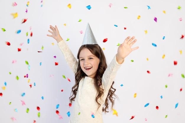 Uma jovem no seu aniversário de princesa com um chapéu com os braços estendidos, gritando sobre um fundo branco isolado, uma linda jovem sorrindo com uma cara feliz