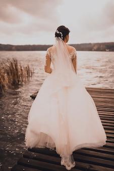 Uma jovem noiva com cabelo ruivo cacheado vestido de noiva branco fica no cais de madeira marrom no meio do lago azul-celeste.
