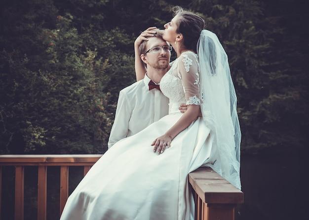 Uma jovem noiva e um noivo juntos ao ar livre, horário de verão