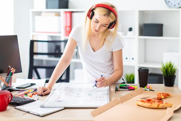 Uma jovem nos fones de ouvido fica perto da mesa e detém um marcador na mão sobre a mesa é um quadro magnético
