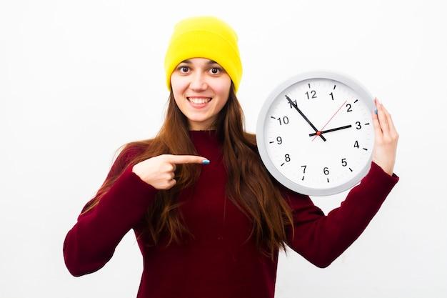Uma jovem olha em um quadro e sorri nas mãos segura um relógio e aponta um dedo para ele