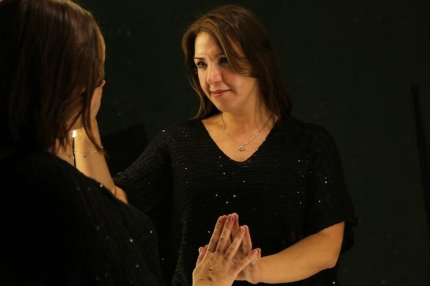 Uma jovem olha para seu reflexo no espelho em casa. espelho de estúdio