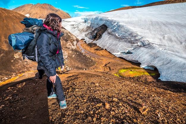 Uma jovem olhando para uma geleira no ponto mais alto da jornada de quatro dias de landmannalaugar. islândia