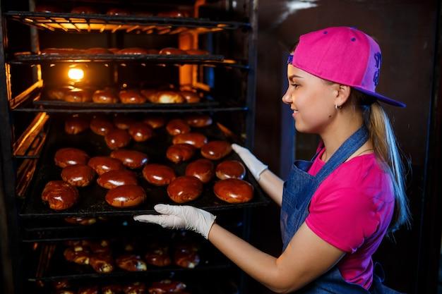 Uma jovem padeiro segura uma bandeja com bolos quentes no fundo de um forno industrial em uma padaria. produção de produtos de panificação.