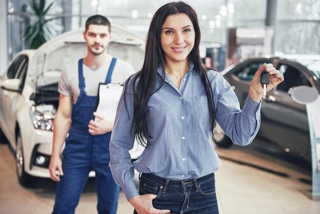 Uma jovem pega um carro no centro de serviço do carro. ela está feliz porque o trabalho é feito perfeitamente