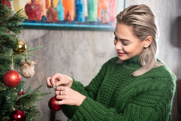 Uma jovem pendura uma árvore de natal em um galho de pinheiro