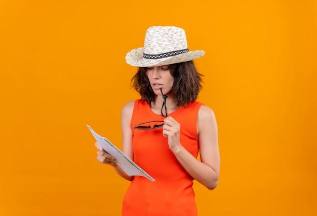 Uma jovem pensativa, com cabelo curto e uma camisa laranja com chapéu de sol, olhando para um mapa