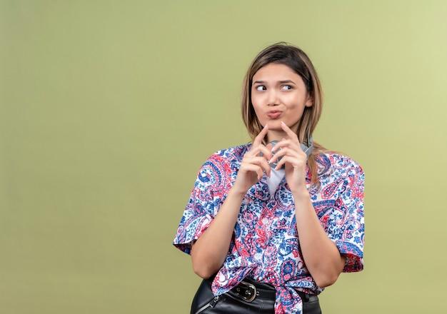 Uma jovem pensativa com uma camisa estampada de paisley usando fones de ouvido, pensando enquanto olha para o lado
