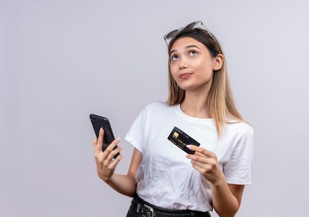 Uma jovem pensativa, com uma camiseta branca e óculos de sol, pensando enquanto segura o celular e o cartão de crédito