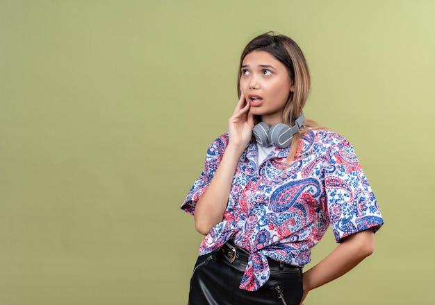 Uma jovem pensativa, vestindo uma camisa estampada de paisley em fones de ouvido, pensando com as mãos no rosto enquanto olha para cima